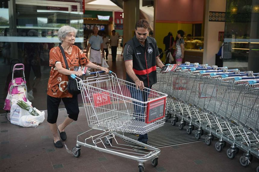 A trolley enforcement officer helping a customer return her trolley outside Jurong Point.