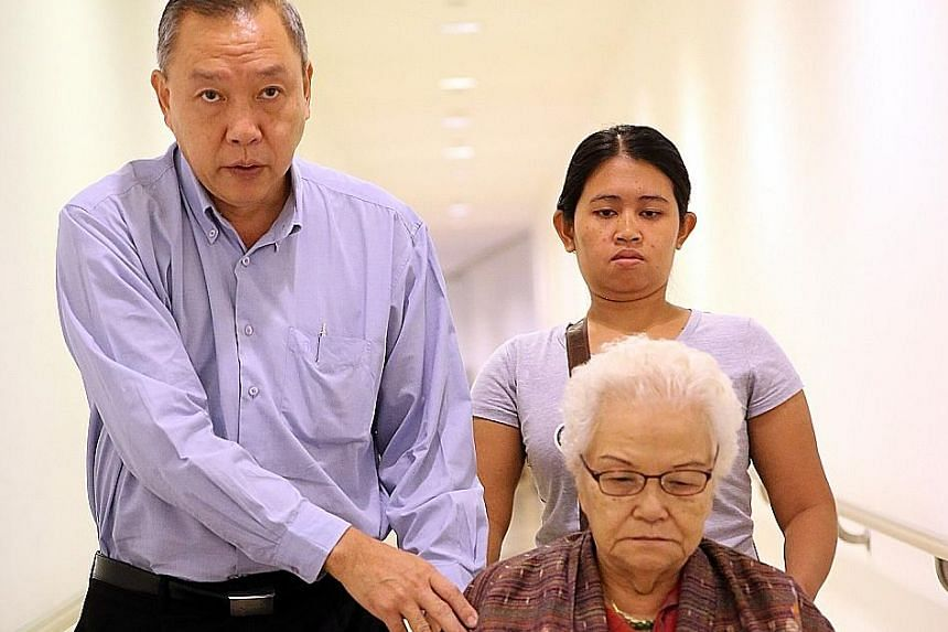 Sheng Siong supermarket boss Lim Hock Chee with his 81-year-old mother, Madam Ng Lye Poh, who testified yesterday, leaving the court with their domestic worker.