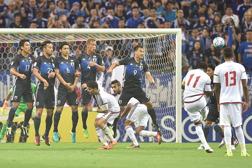United Arab Emirates forward Ahmed Khalil (No. 11) equalises with a 20th-minute free kick. He went on to score the winner from the penalty spot, handing Japan a 2-1 loss in the World Cup qualifier.