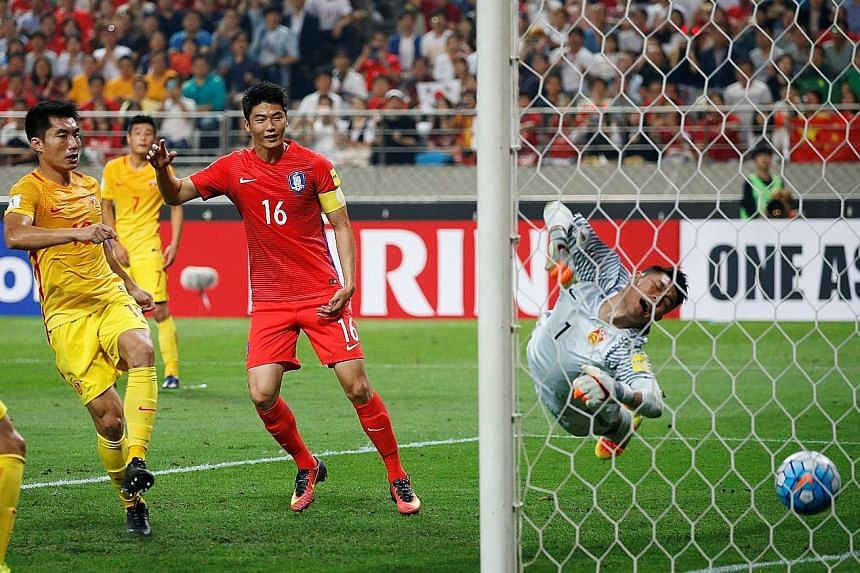 South Korean captain Ki Sung Yeung (red jersey) starts to celebrate as the ball crosses China's goal-line in their narrow 3-2 victory in Seoul yesterday.
