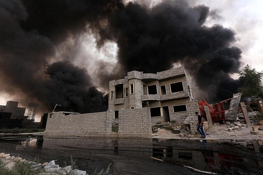 Smoke billowing from oil wells that were set ablaze by ISIS militants before they fled from Iraqi forces in Qayyarah, the northern town on the banks of the Tigris river, on Tuesday.