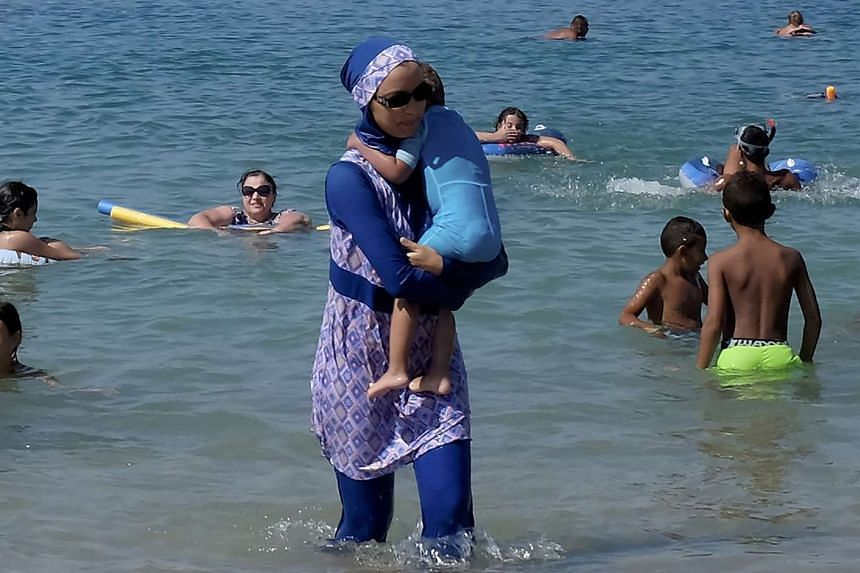A woman wearing a burkini walks in the water on Aug 27, 2016, on a beach in Marseille, France,  the day after the country's highest administrative court suspended a ban on full-body burkini swimsuits.