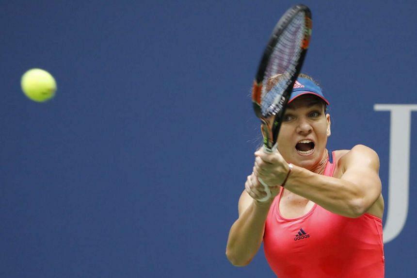 Simona Halep of Romania hits a return to Kirsten Flipkens of Belgium.