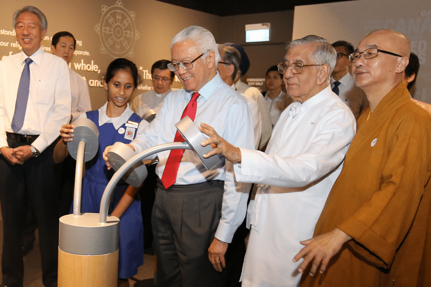 President Tony Tan interacts with a student from St. Nicholas Girls' School at the Harmony in Diversity Gallery.