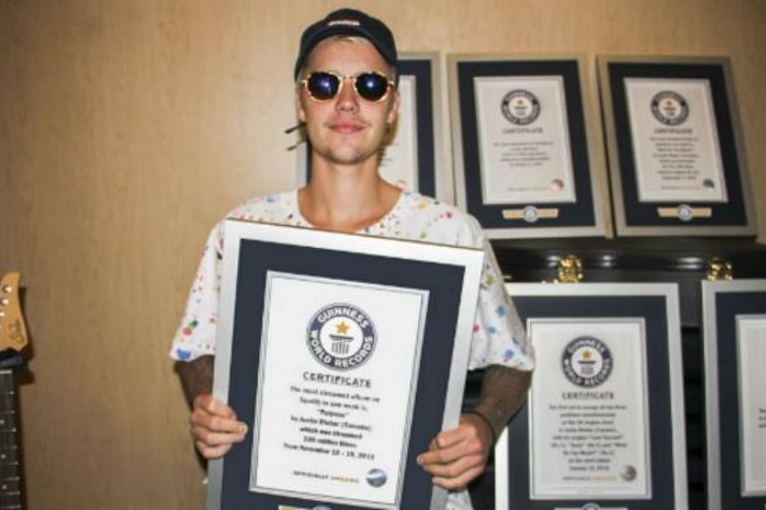 Pop star Justin Bieber posing with his eight Guinness World Records certificates.