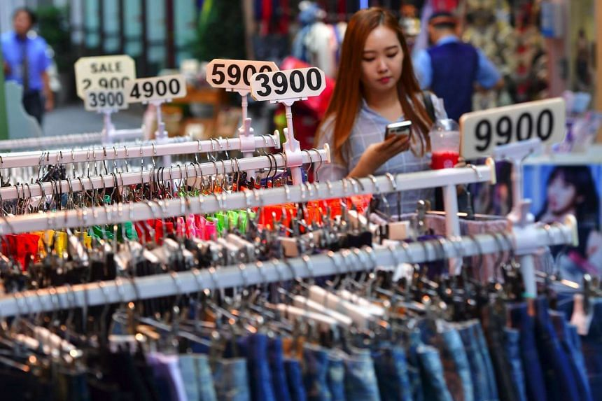 A woman walks past clothing displayed by various prices at a shopping district in Seoul on July 26, 2016.