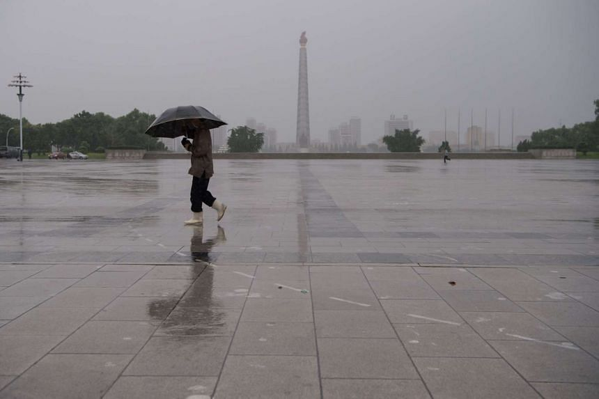 A woman holding an umbrella walks before the Tower of the Juche Idea, on Kim Il Sung square during rainfall in Pyongyang on July 16, 2016.