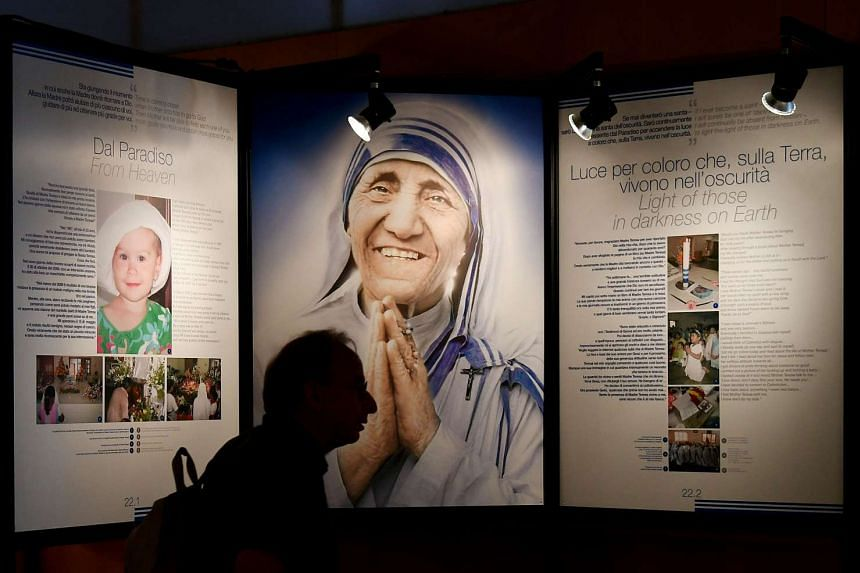 A visitor passing by pictures of Mother Teresa during a photograph exhibition held in Rome on Sept 1, 2016.