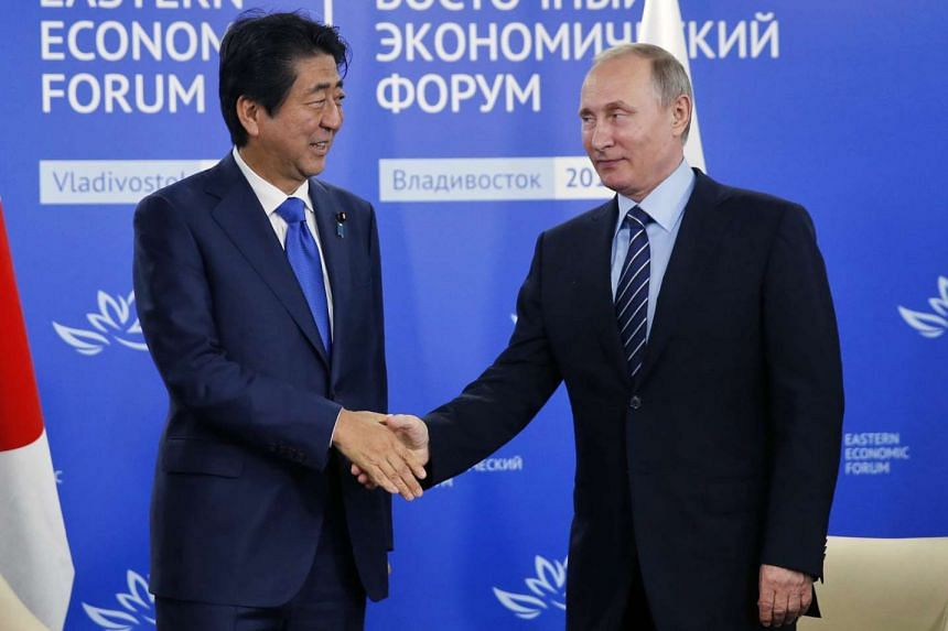Russian President Vladimir Putin (right) shaking hands with Japanese Prime Minister Shinzo Abe (left) at the Eastern Economic Forum in Vladivostok, Russia on Sept 2, 2016.