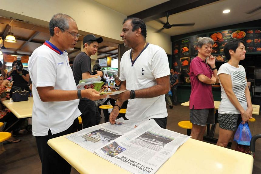 Minister for the Environment and Water Resources Masagos Zulkifli (left) handing out a booklet to Mr K. Mohan, 57, on mosquito prevention and Zika at a coffeeshop at Tampines Street 81 on Sept 3.
