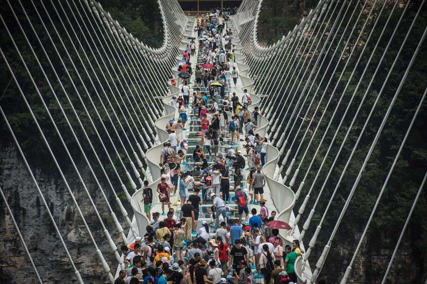 Visitors crossing the world's highest and longest glass-bottomed bridge in Zhangjiajie in China's Hunan Province on Aug 21, 2016.