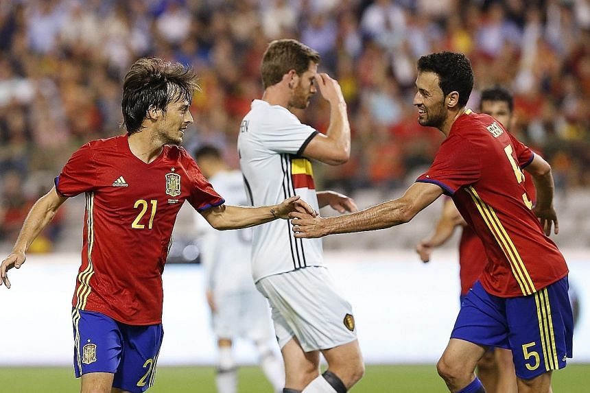 Spain's David Silva (left) celebrating his goal with Sergio Busquets during the friendly match against Belgium on Thursday. Silva scored both goals in the 2-0 win, which will be a boost before their first World Cup qualifier against Liechtenstein.