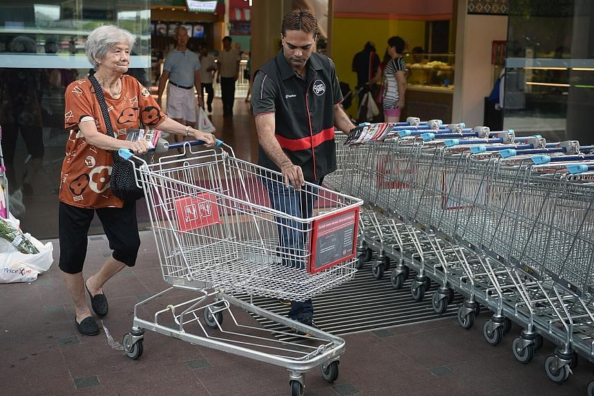 Left: Trolley enforcement officer Kasinathan Sugumaran, 41, helping a FairPrice Xtra customer return her trolley outside Jurong Point. The two FairPrice outlets at the mall have seen 150 to 200 trolleys abandoned daily this year. Above: A bunch of un