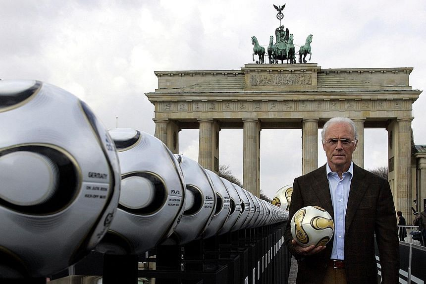 Franz Beckenbauer, the president of Germany's World Cup organising committee, holding a ball next to Brandenburg Gate in 2006. The football legend is now assisting a Swiss investigation into corruption allegations over the awarding of the 2006 World