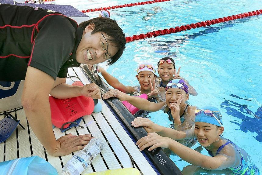 Tokyo Swimming Club head coach Yoshida Takahiro (left) with (from right) Reon Kashiwagi, Chishina Wada, Kokomi Maekawa and Hijiri Yamada during a training session at the Chinese Swimming Club yesterday. Nine Japanese swimmers aged between 11 and 12 a