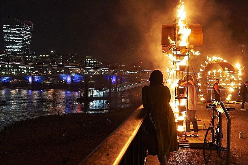 """A """"Fire Garden"""", designed by French fire masters Compagnie Carabosse, being performed outside the Tate Modern in central London on Thursday as part of the London's Burning festival of events commemorating the 350th anniversary of the Great Fire of Lo"""