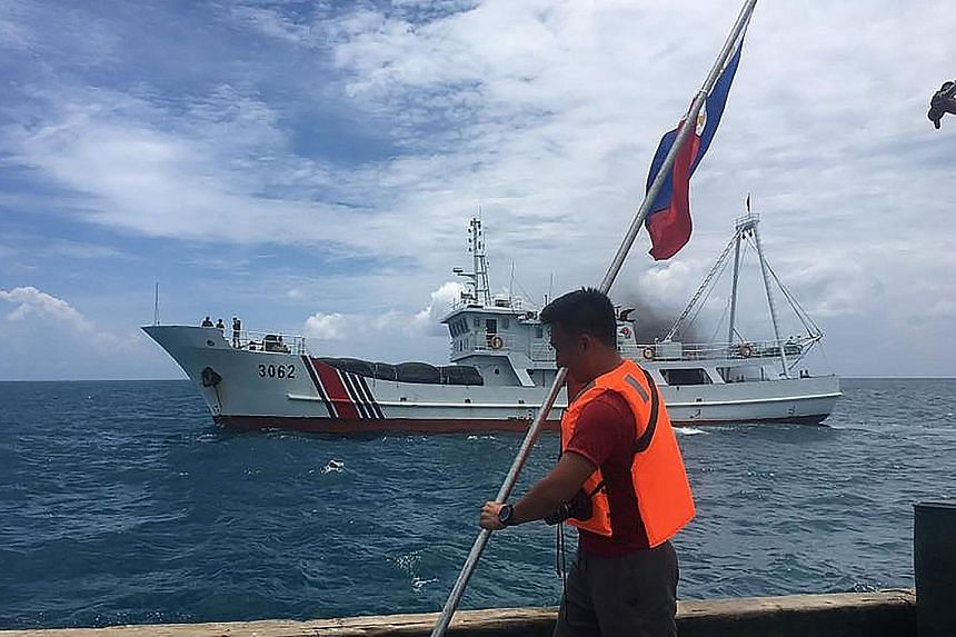 A Philippine activist holding his country's flag while a Chinese coast guard vessel sails near his ship at the Scarborough Shoal, just 220km west of the main Philippine island of Luzon.