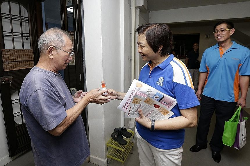 Nee Soon GRC MP Lee Bee Wah giving insect repellent to 71-year-old retiree Goh Han Kiat during her door-to-door visit at Block 826, Yishun Street 81, yesterday.