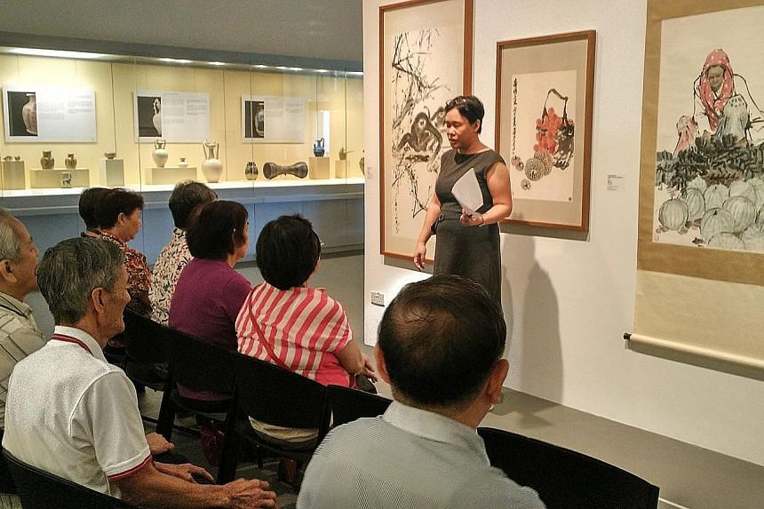 Seniors in an art reminiscence therapy session at NUS Museum. Six volunteer museum guides are trained to understand group dynamics, know how to elicit emotions and use paintings to relate to the seniors' memories and life experiences.