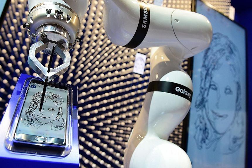 Left: A robot drawing a portrait on a Galaxy Note7 smartphone at the Samsung booth at the IFA fair in Berlin on Thursday. Above: A hoverboard by Beamie at the company's stand at the fair.