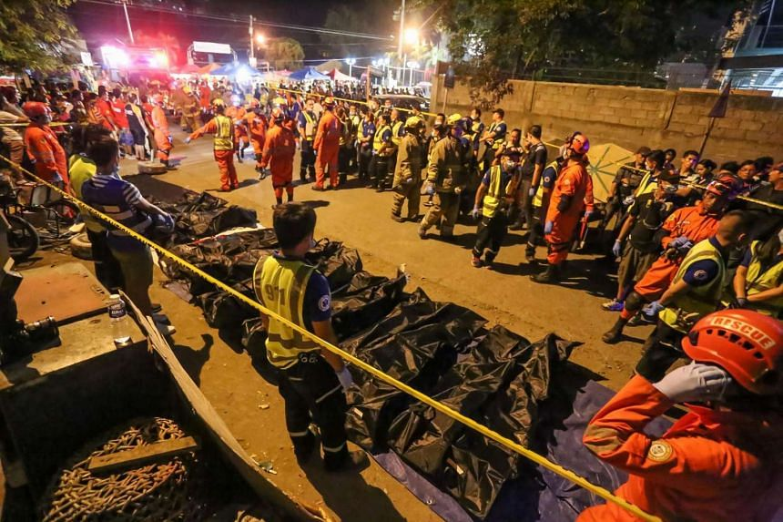 Rescue workers gathering bags containing dead bodies of victims of an explosion at a night market in Davao City in southern island of Mindanao, early Sept 3, 2016.