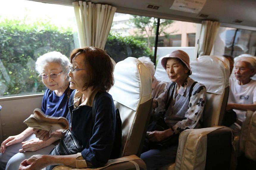 Elderly people boarding a bus as they leave the Kirigaoka Day Home in Kita ward in Tokyo, Japan, on June 16, 2015.