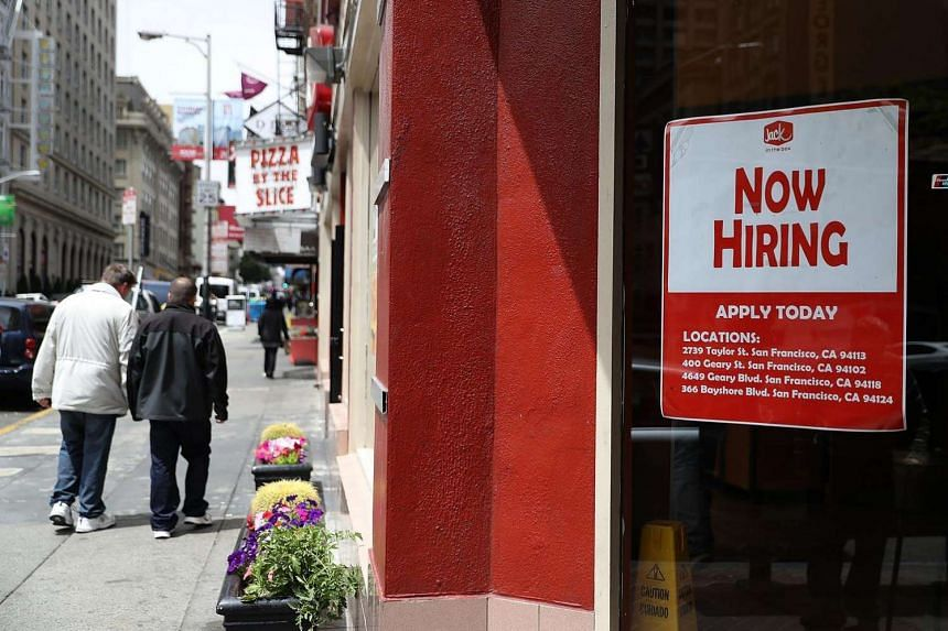 A 'Now Hiring' sign is posted in the window of a fast food restaurant on July 8, in San Francisco, California.