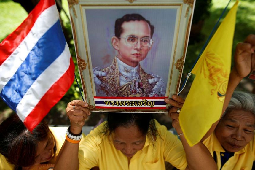Well-wishers hold a picture of Thailand's King Bhumibol Adulyadej at Siriraj hospital in Bangkok on June 9, 2016.