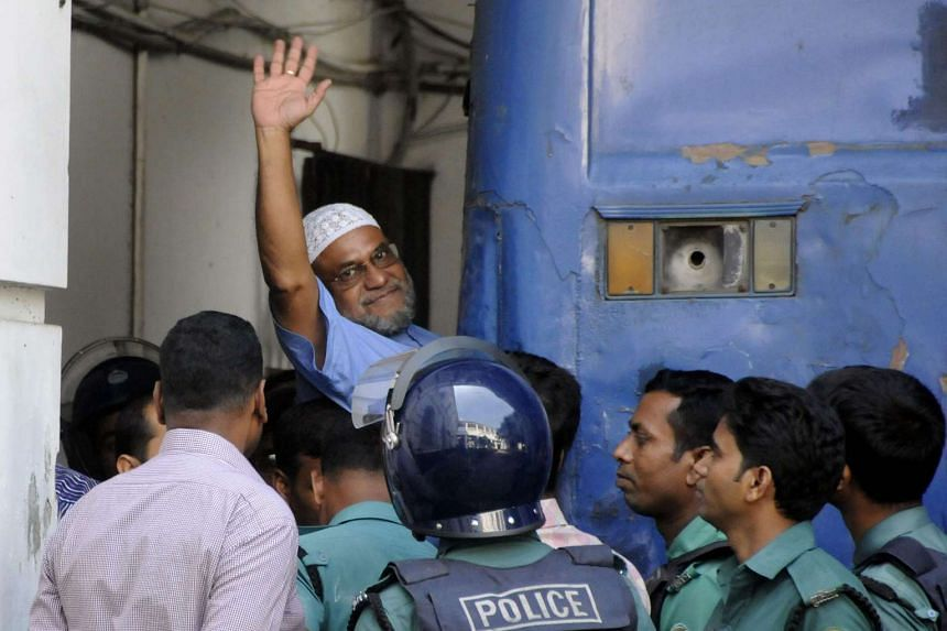 Mir Quasem Ali waves as he enters a van at the International Crimes Tribunal court in Dhaka on Nov 2, 2014.