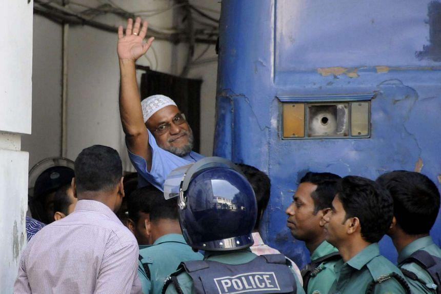 Mir Quasem Ali waves as he enters a van at the International Crimes Tribunal court in Dhaka on Nov 2, 2014.