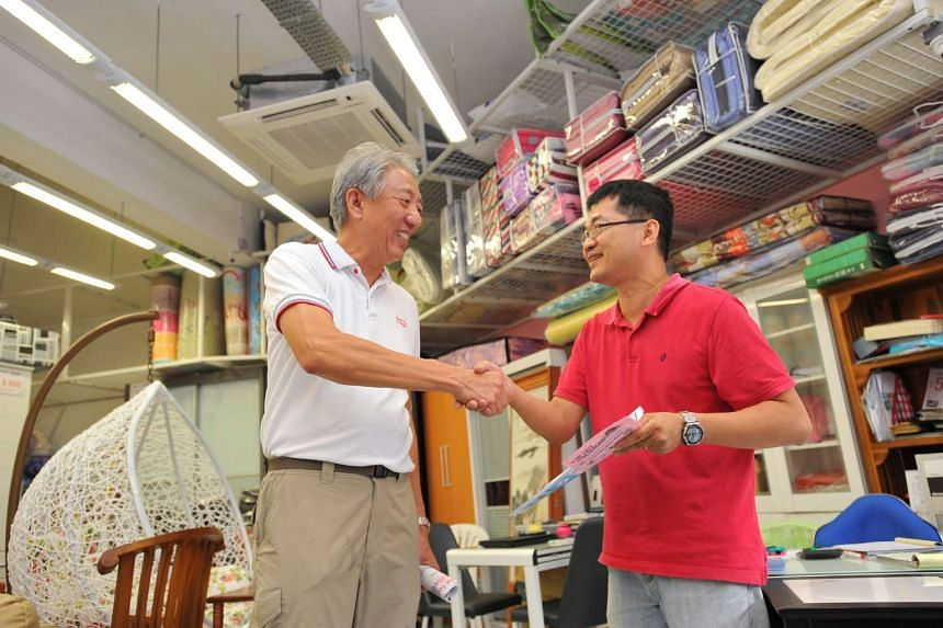 DPM Teo Chee Hean shaking hands with Mr Jimmy Lee, 44, sales manager of Qi Wen Furniture, after explaining about mosquito prevention and Zika at Pasir Ris West Plaza on Sept 3, 2016.