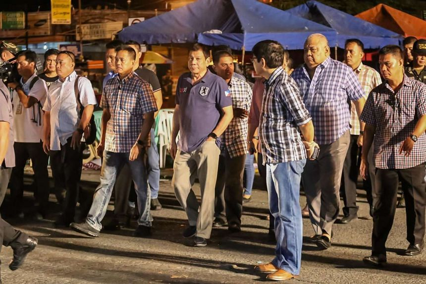 Philippine President Rodrigo Duterte (centre) arriving at the site of an explosion at a NIGHT market in Davao City in southern island of Mindanao, early Sept 3, 2016.