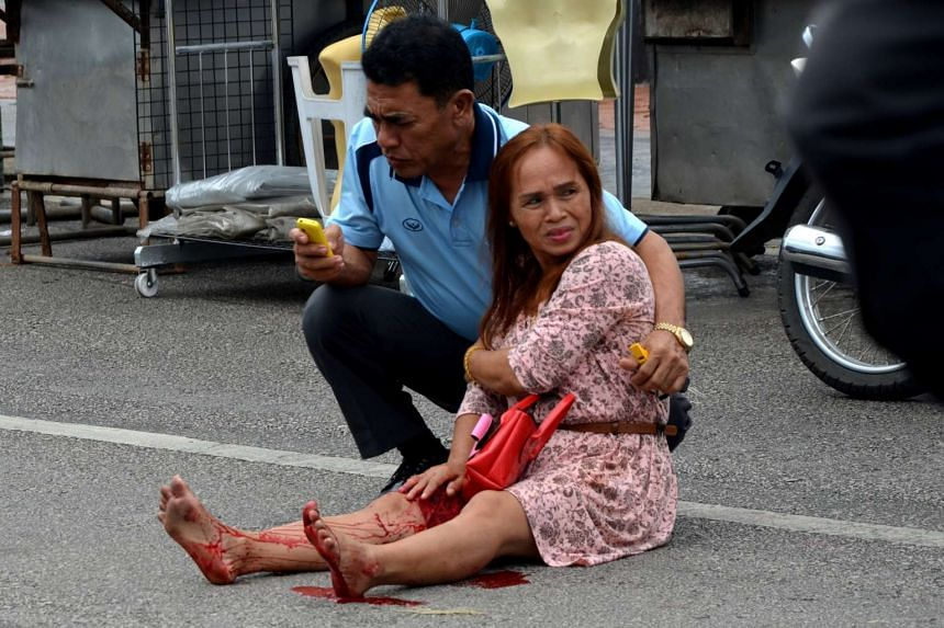 An injured woman is given assistance after a bomb exploded on Aug 11, 2016, in Trang, Thailand.