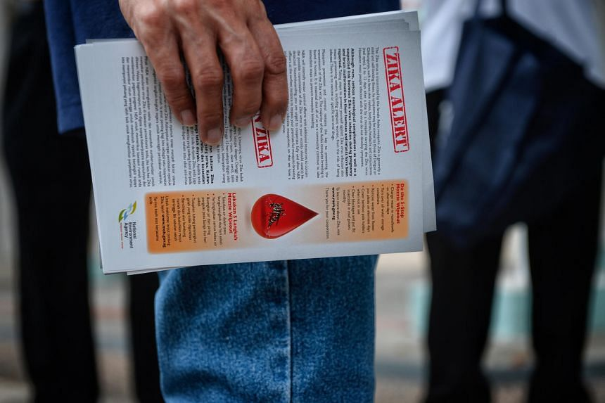 A Town Council member holding an informational Zika leaflet before giving them out to residents on Sept 1, 2016.