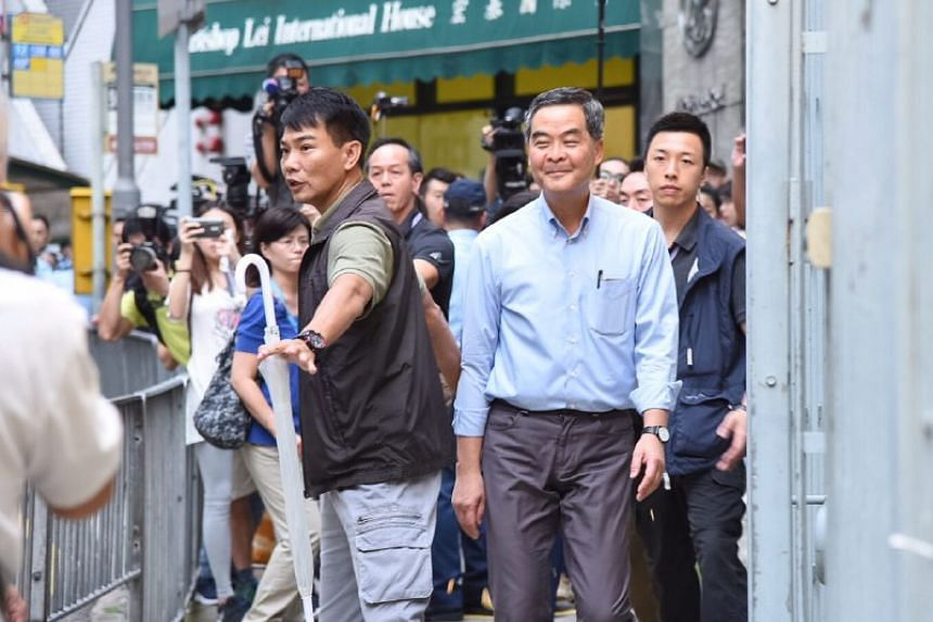 Chief Executive Leung Chun Ying arrived at a polling station at the mid levels, jeered by radical pan-democrats Leung Kwok Hung and Avery Ng, who were standing across the road.
