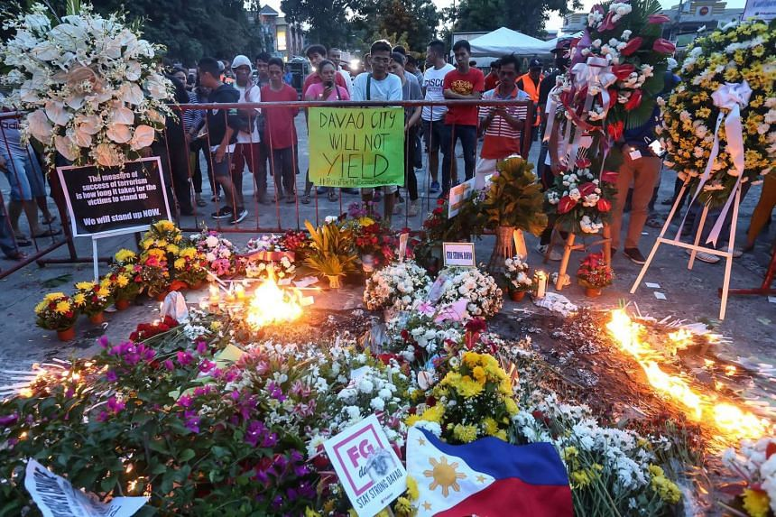 Residents light candles and place flowers as they offer prayers for bomb blast victims at a night market, during a memorial at the site in Davao City on Sept 3, 2016.