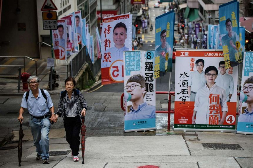 An elderly couple walk past campaign banners during the Legislative Council election in Hong Kong on Sept 4, 2016.