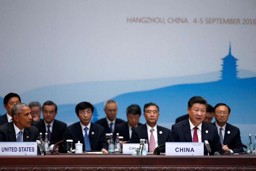 Chinese President Xi Jinping speaks as US President Barack Obama looks on, as they attend the opening of the G20 Summit in Hangzhou.