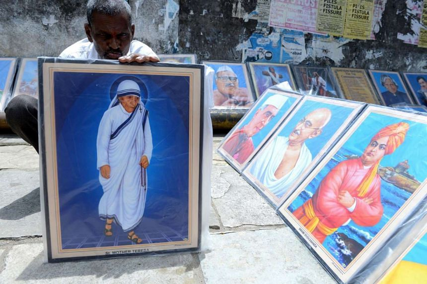 An Indian vendor arranges a photograph of Mother Teresa on a street in Secunderabad, the twin city of Hyderabad on Sept 4, 2016, ahead of the canonisation of Mother Teresa in Rome.