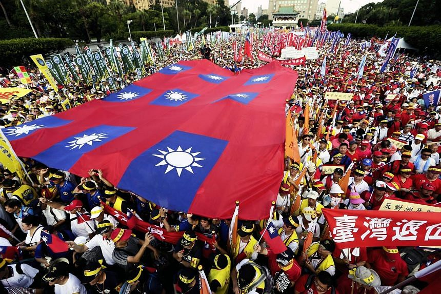 Protesters holding up flags and banners in Taipei yesterday. Organisers estimated the turnout for the three-hour march to be 250,000, but the police put the figure at only 150,000.