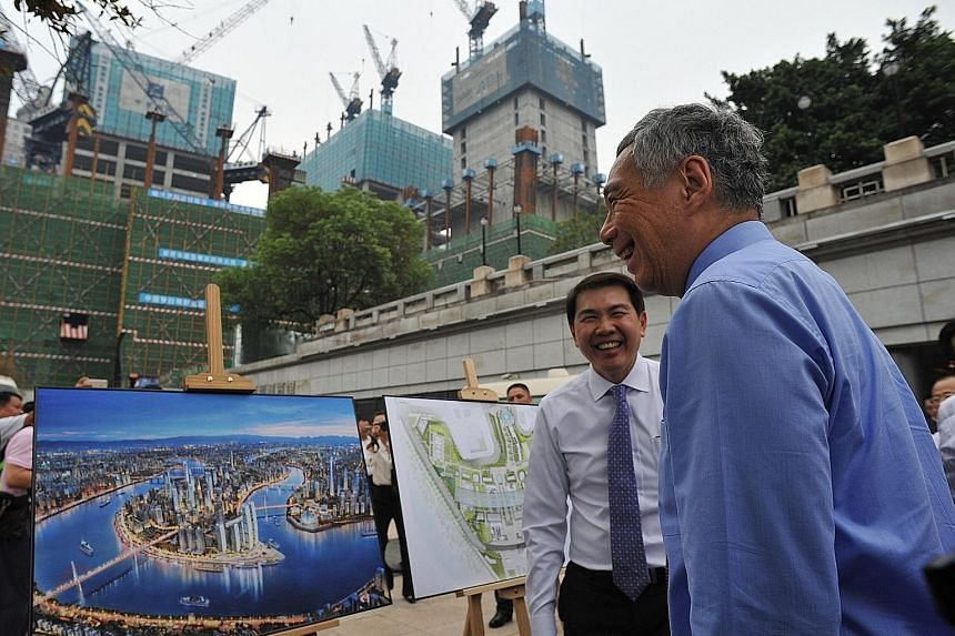 CapitaLand group CEO Lim Ming Yan updating PM Lee on Raffles City Chongqing during his visit yesterday. The $4.9 billion residential and commercial development is the biggest single investment by a Singapore firm in China.