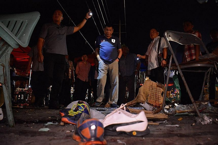 Mr Duterte (centre, in blue shirt) inspecting the site of the explosion at a night market in Davao city, Philippines.