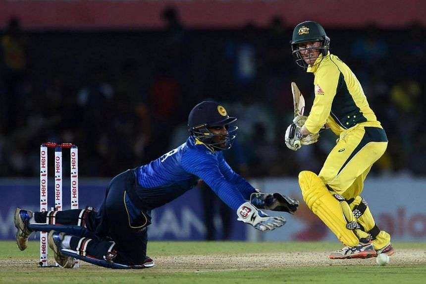Australian cricketer George Bailey (right) plays a shot as Sri Lanka's wicketkeeper Kusal Perera looks on during the fourth ODI cricket match between Sri Lanka and Australia on Aug 31.