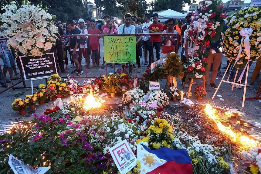 Residents light candles and place flowers for bomb blast victims  during a memorial at the site in Davao City, on Sept 3, 2016.
