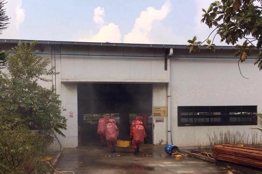 SCDF Hazmat personnel moving into an indoor storage facility to plug a chlorine gas leak, in Tuas, on Sept 4, 2016.