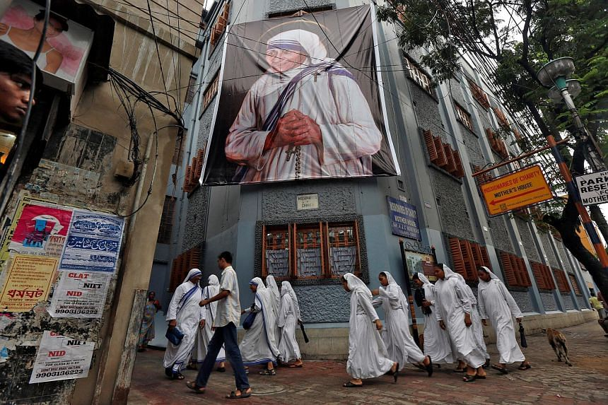 Nuns belonging to the global Missionaries of Charity, walk past a large banner of Mother Teresa ahead of her canonisation ceremony, in Kolkata, India on Sept 3, 2016.