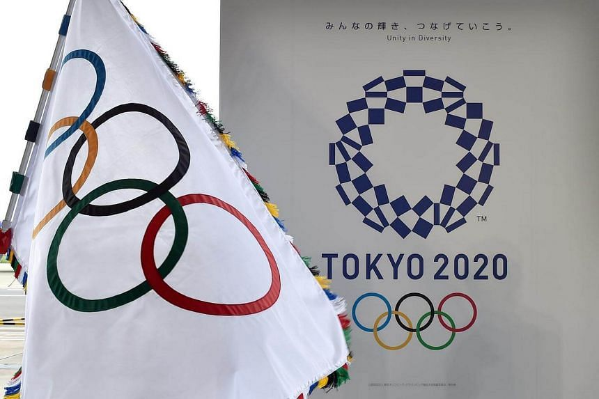 The Olympic flag (left) and the logo of the Tokyo 2020 are displayed during the official flag arrival ceremony at the Tokyo's Haneda airport on Aug 24, 2016.
