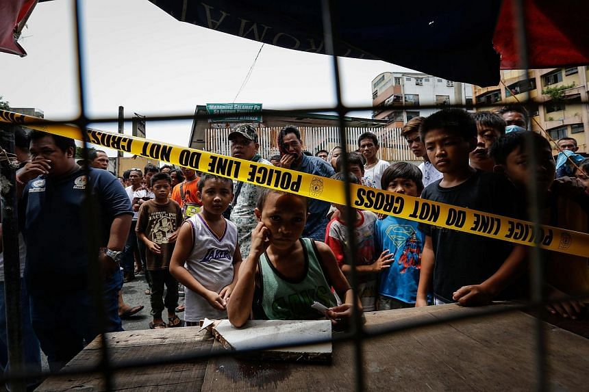 Filipinos looking outside a cordoned area following a police operation against illegal drugs in Manila, Philippines on Aug 28, 2016.