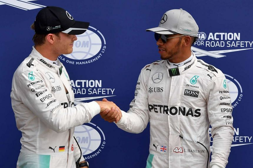 Rosberg shakes hands with Mercedes team-mate Lewis Hamilton after Hamilton wins pole position.