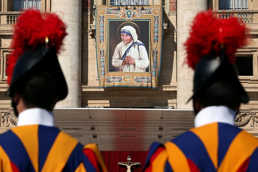 Guards stand in front of a tapestry depicting Mother Teresa of Calcutta before a mass, celebrated by Pope Francis, for her canonisation in Saint Peter's Square at the Vatican on Sept 4, 2016.